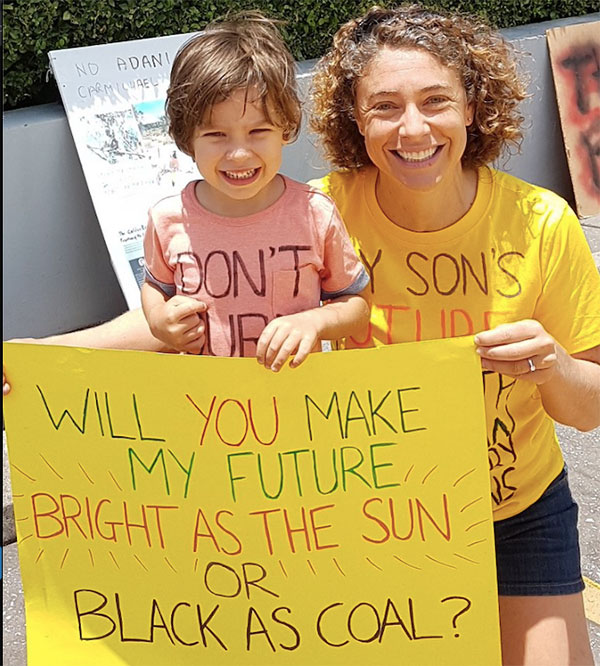 Mother and child holding up a sign