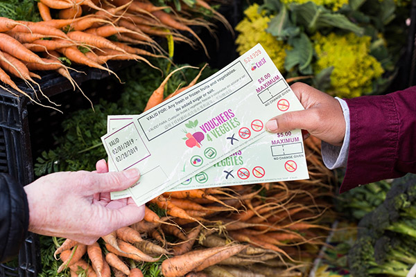 Two people holding Vouchers 4 Veggies coupons