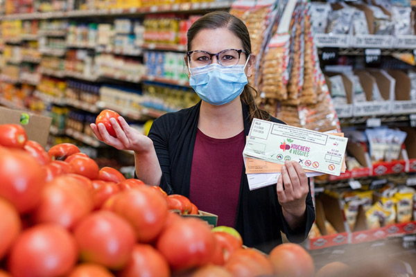 Woman holding a tomato in a grocery store