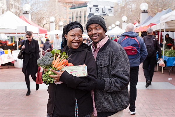 Man and woman holding vegetables