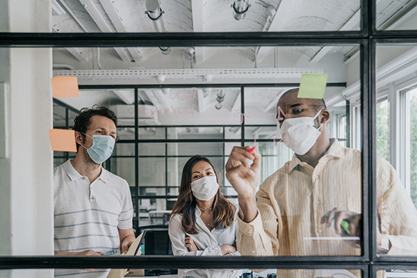 People brainstorming at whiteboard while wearing masks