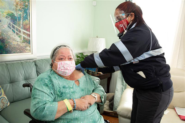 Person receiving vaccine shot at home