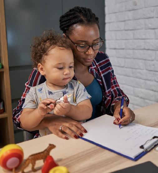 Woman holding a baby while writing at a desk