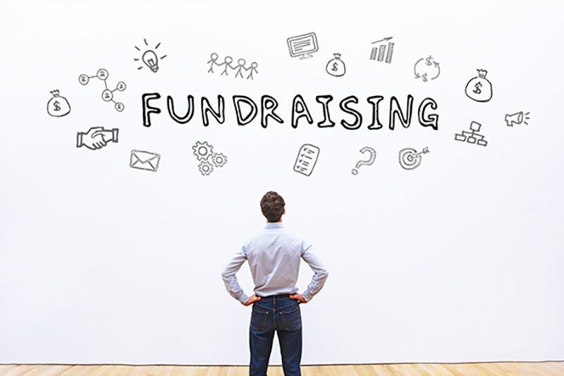 Man facing a wall with fundraising graphic
