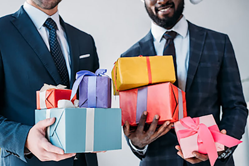 Businessmen holding wrapped gifts