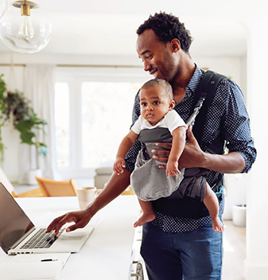 Father with child at laptop in kitchen