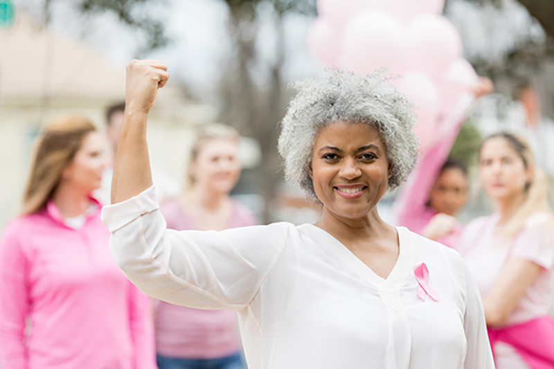 Breast cancer survivor flexing and smiling