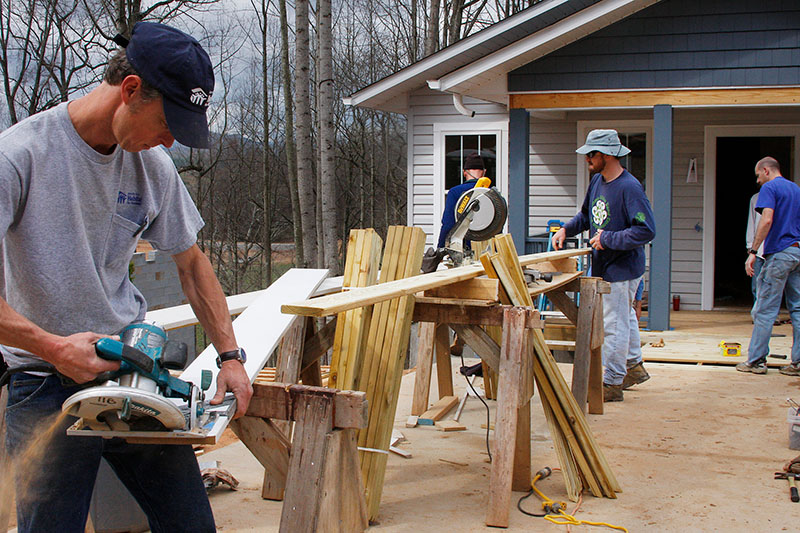 Volunteers cutting wood for a new home
