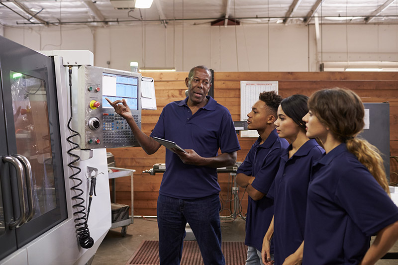 Man teaching group of people how to work a machine