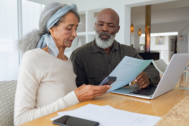 Man and woman sitting at table looking at documents