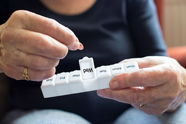 Person holding medication container