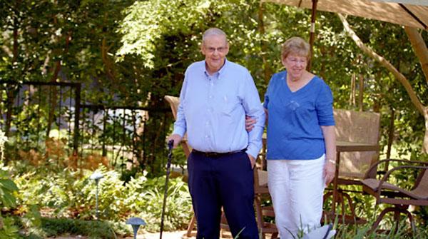 Man and woman walking through a garden