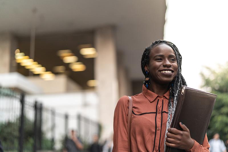 Female student smiling on university campus.