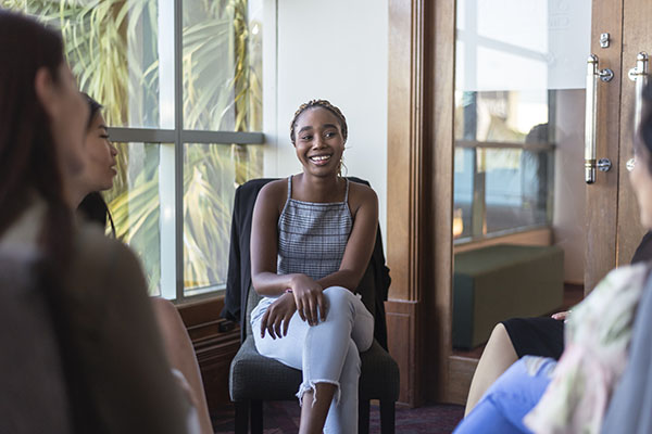 Woman smiling while sitting in a conversation circle