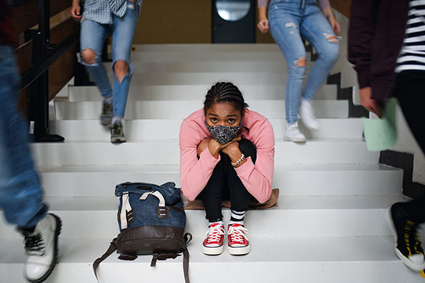 Young girl wearing a mask while sitting on steps
